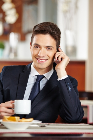 having breakfast: Businessman making phone call at breakfast in coffee shop with his smartphone