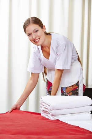 Smiling hotel maid making the bed in a hotel room photo