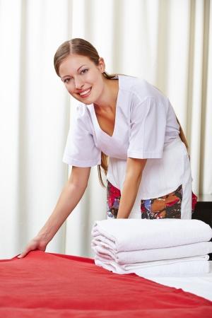 sirvienta: Sonriendo camarera de hotel hacer la cama en una habitación de hotel