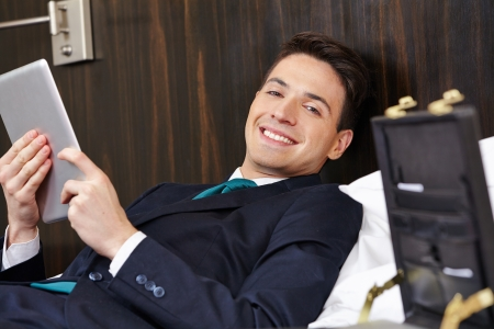 Smiling manager using a tablet computer in hotel room bed photo