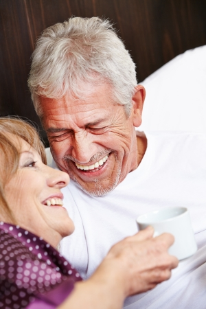 eroticism: Two happy seniors laughing together in a bed