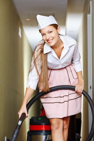 Happy cleaning lady with vacuum cleaner cleaning a hotel floor photo