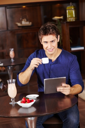 having breakfast: Man with tablet computer drinking coffee in a hotel