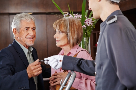 porter: Senior people taking key card from concierge in a hotel