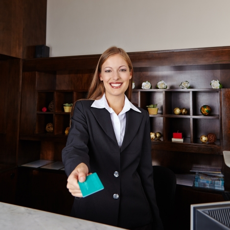 Happy receptionist in hotel offering key card to room Фото со стока