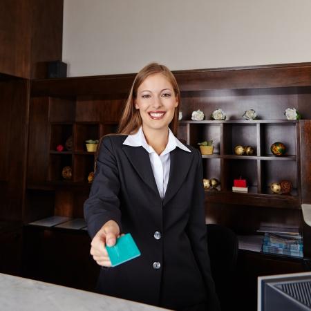 recepcionista: Recepcionista feliz en el hotel que ofrece la tarjeta llave de la habitaci�n Foto de archivo
