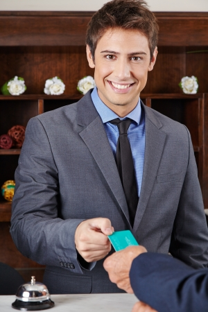 Smiling receptionist in hotel giving key card to guest Stock Photo - 20150712