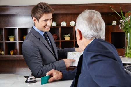 Senior guest in hotel asking receptionist for the way photo