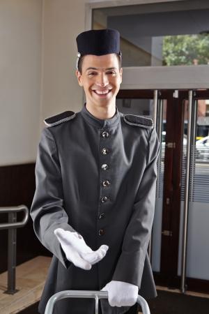 bellhop: Concierge feliz en uniforme de pie en el vest�bulo de un hotel Foto de archivo