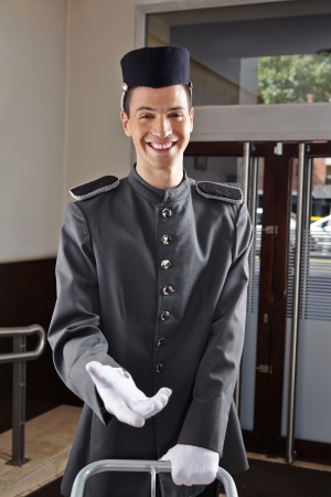 Happy concierge in uniform standing in a hotel lobby photo