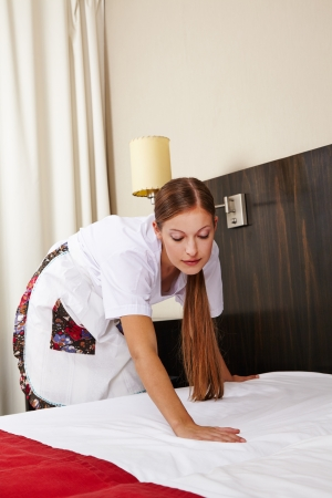 Cleaning lady in hotel making bed during housekeeping photo
