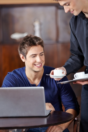 Waiter in café serving man a hot cup of coffee photo