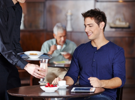 Waiter bringing man a cocktail in a hotel photo