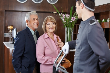 porter: Senior couple at check-in at hotel looking at concierge Stock Photo