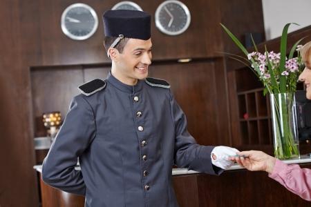 bellhop: Amistoso concergie en el hotel con una tarjeta de clave de la mujer mayor Foto de archivo