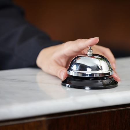 Female hand ringing hotel bell at the counter with index finger photo