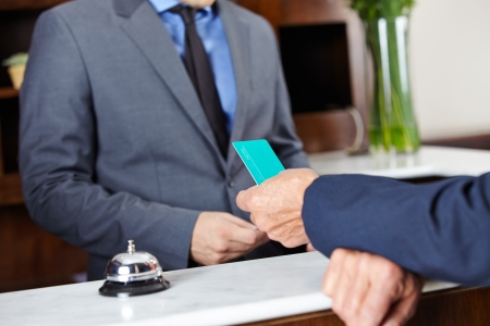 Leaving guest giving his room key card to hotel receptionist photo