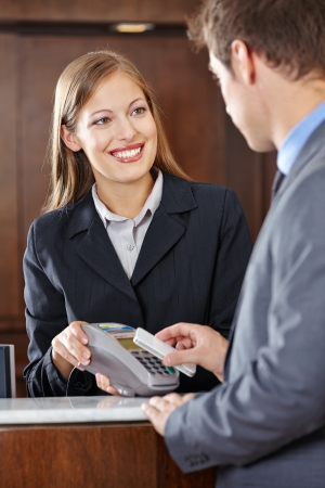 hotel staff: Guest in hotel paying bill with smartphone via NFC technology Stock Photo