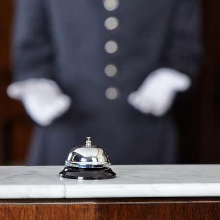 bellhop: Concierge with white gloves pointing to hotel bell on counter Stock Photo