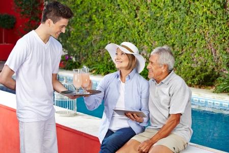sirvientes: Pareja mayor que toma un cóctel en la piscina del hotel de camarero