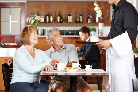 Waiter serving two seniors in a coffee shop for breakfast photo