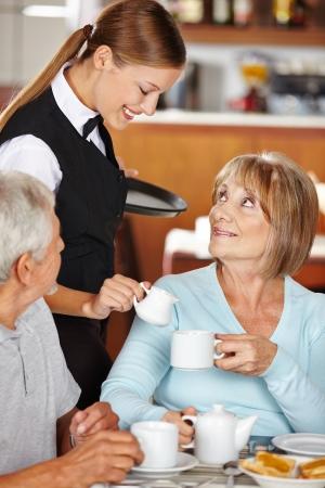 Waiter serving senior woman milk to coffee in coffee shop photo
