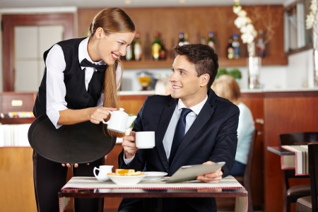 Businessman in coffee shop flirting with female waiter photo