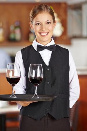 camarero: Camarero femenino feliz con dos vasos de vino tinto en un restaurante