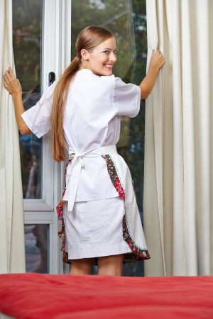 Hotel maid pulling up curtains in a hotel room photo