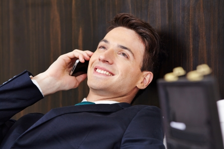 Happy manager making a phone call in hotel room with his smartphone Stock Photo - 20150761