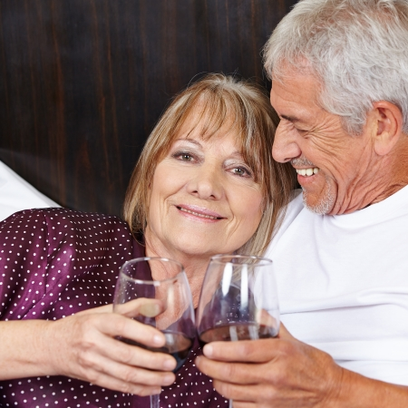 love affair: Happy senior couple drinking red wine in bed
