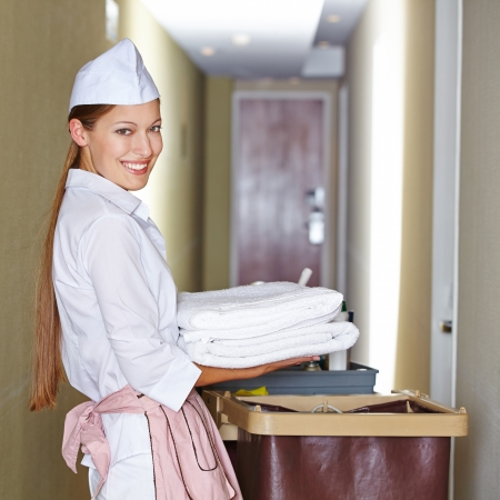 hotel staff: Smiling hotel maid with fresh towels doing housekeeping Stock Photo