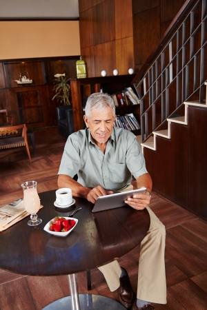 Happy senior man using tablet PC in hotel lobby Stock Photo - 20281107