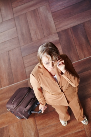 Old woman traveling with luggage talking on the phone Stock Photo - 20277934