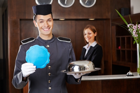hospitality: Friendly bellboy holding empty sign in hotel with receptionist behind counter