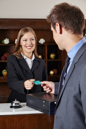 Businessman in hotel at reception getting his room key card Stock Photo - 20294789