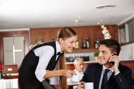 busy restaurant: Waiter offering a pot of coffee to business man in hotel café Stock Photo