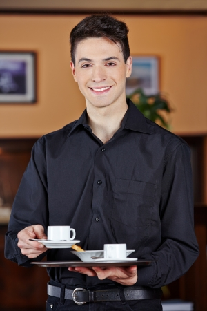 Smiling waiter bringing hot cup of coffee in a café photo
