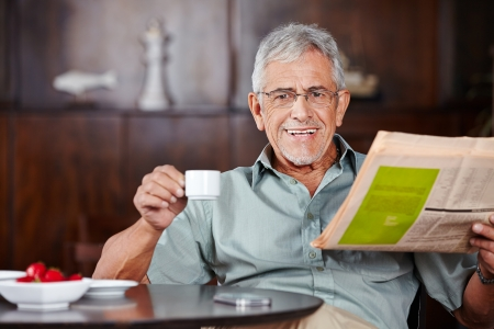 old people smiling: Happy senior man sitting with coffee and newspaper in a café Stock Photo