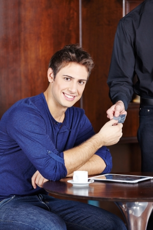Young man in café paying his coffee with a credit card photo