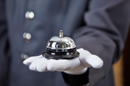 Hand van een conciërge met een hotel bell Stockfoto