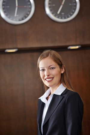 Smiling female receptionist standing at hotel counter photo