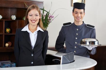recepcion: Concierge feliz y recepcionista en el hotel esperando en el mostrador Foto de archivo