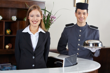 Happy concierge and receptionist in hotel waiting at counter photo