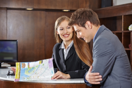 hospitality staff: Smiling receptionist in hotel helping a guest with a city map Stock Photo