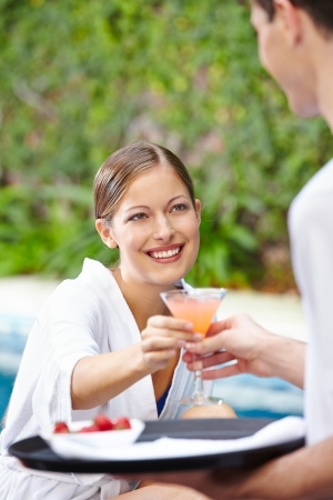 Happy woman drinking a cocktail at pool of hotel Stock Photo - 20281097