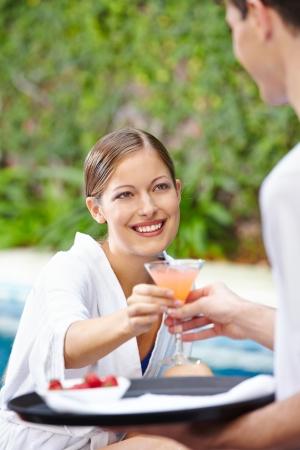 meseros: Mujer feliz bebiendo un c�ctel en la piscina del hotel, Foto de archivo
