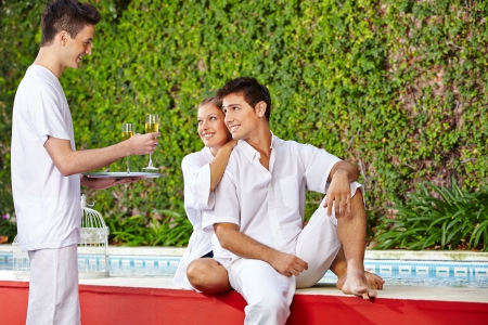 Happy couple sitting at the pool getting champagne from a waiter Stock Photo - 20294409
