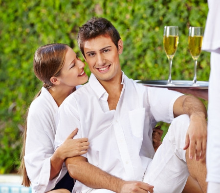 Happy young holiday couple at pool with champagne photo