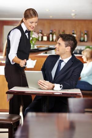 Vrouwelijke ober serveert zakenman in koffie winkel een pot koffie